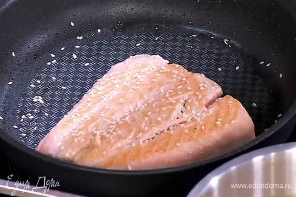 Разогреть в сковороде немного кунжутного масла, выложить семгу кожей вниз, сбрызнуть кунжутным маслом и прогревать на среднем огне, пока рыба снизу не посветлеет, затем перевернуть ее, посыпать щепоткой кунжута и жарить до готовности.