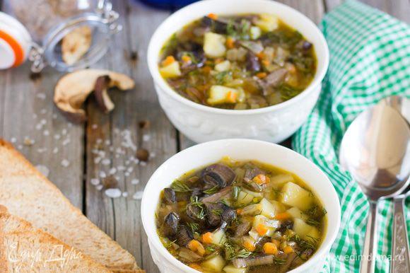 В кастрюлю налейте овощной бульон, доведите до кипения, и забросьте в него картофель и варите 7 минут, постоянно снимая пенку. Затем добавьте размороженные белые грибы, обжаренный лук и морковь, и варите 15 минут. Приправьте по вкусу и посыпьте рубленой зеленью! Подавайте грибной суп с чесночными гренками. Приятного аппетита!