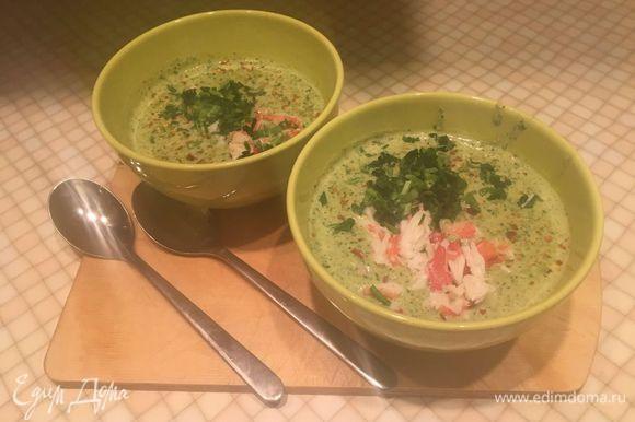 Разлить суп по тарелкам. Сверху выложить мясо краба. Украсить листьями петрушки и красным перцем. Приятного аппетита.