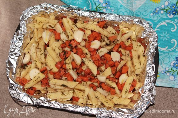 Жаростойкую форму для выпекания выстелить фольгой для запекания, чтобы овощи не пригорели и сохранился маринад. Выложить овощи и сверху выложить чеснок (9-10 небольших зубков, если очень крупный то порезать на 2-4 части).