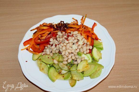 Горячие овощи выложить вместе с маслом на тарелочку, добавить фасоль. Посыпать мелко нашинкованным чесноком и перемешать.