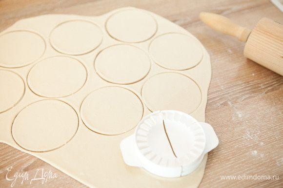 Раскатываем тесто тонким пластом толщиной 2 мм. Поверхность заранее припорошив мукой. Вырезаем стаканом кружки, я использую специальное приспособление для вареников. Замороженные ягоды высыпаем в дуршлаг и даем оттаять.