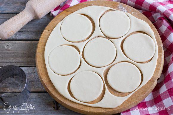 Тесто раскатайте на присыпанной мукой поверхности в пласт толщиной 2 мм. С помощью стакана или круглой кондитерской форму вырежьте кружочки из теста диаметром 6 см.