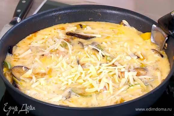 В сковороду с овощами добавить ветчину, сверху вылить яично-молочную массу и посыпать натертым сыром.