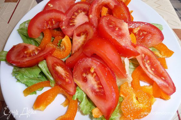 Перец нарезать произвольно, помидор нарезать дольками. Выложить на лист салата, присыпать чесночным порошком.
