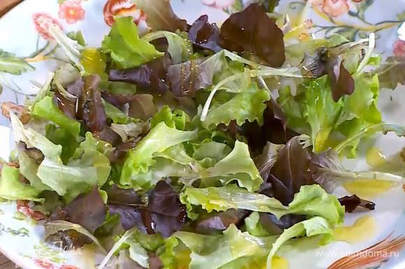 Листья салата выложить на блюдо и сбрызнуть оливковым маслом.