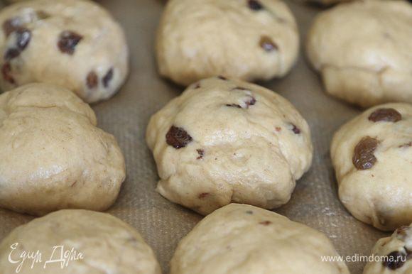 Подошедшее тесто разделить на небольшие шарики, выложить на противень, застеленный бумагой для выпечки. Накрыть салфеткой и оставить еще на 30 минут.