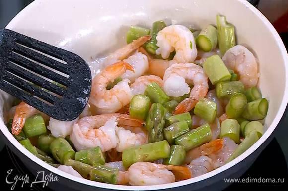 Разогреть в сковороде оливковое масло и обжарить размороженные креветки почти до готовности, затем добавить спаржу и обжаривать все еще 3‒4 минуты.