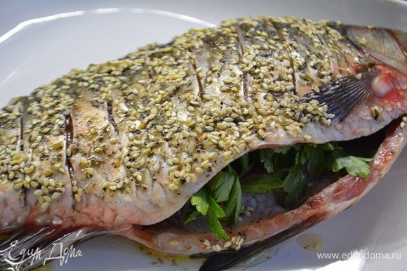Форму смазать маслом и уложить рыбу, брюшко нашпиговать веточками петрушки. Запечь при температуре 200°С, 40 минут.