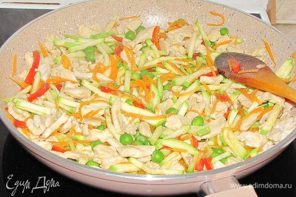 Добавить к мясу нарезанные овощи и зеленый горошек (если замороженный, то предварительно разморозить), мелко рубленный чеснок.