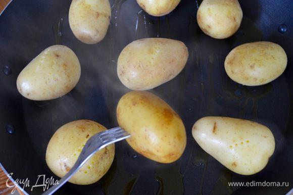 Поднос обильно сбрызнуть оливковым маслом и выложить картофель на небольшом расстоянии друг от друга.