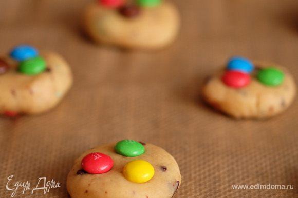 Разогреть духовку до 180°C. Достать тесто из холодильника и формировать печенья: отщипнуть небольшой кусочек теста, скатать шарик (величиной примерно с грецкий орех), сплющить его до толщина 1-1,5 см и уложить на противень, застеленный бумагой для выпечки. Сверху вдавить 2-3 конфетки. Таким образом сформировать печенья из оставшегося теста.