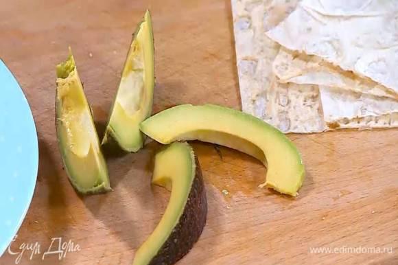 Авокадо почистить, нарезать длинными полосками и сбрызнуть лимонным соком.
