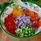 В миску сложить все нарезанные кубиками овощи — перцы, огурец, лук, и помидоры...