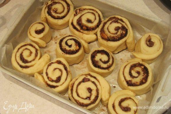Форму для выпечки выстелить пергаментом и слегка смазать его сливочным маслом. Поместить булочки в форму, накрыть пищевой пленкой и оставить на расстойку на 15-20 минут.