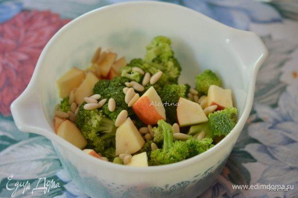 Брокколи очищенный положить в салатное блюдо, добавить очищенное яблоко небольшое, нарезанное кубиками, клюкву и кедровые орешки.