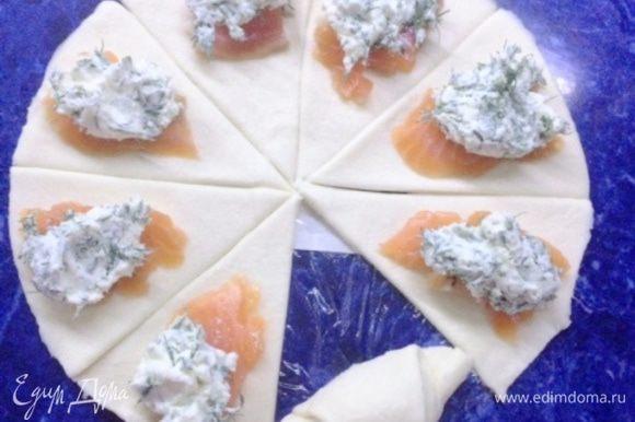 Из 500 г теста у меня получилось вырезать три таких круга для круассанов (получилось 24 штучки). Делим тесто на сегменты. Выкладываем по кусочку рыбы, а сверху ложечку сырной начинки. Сворачиваем круассаны.