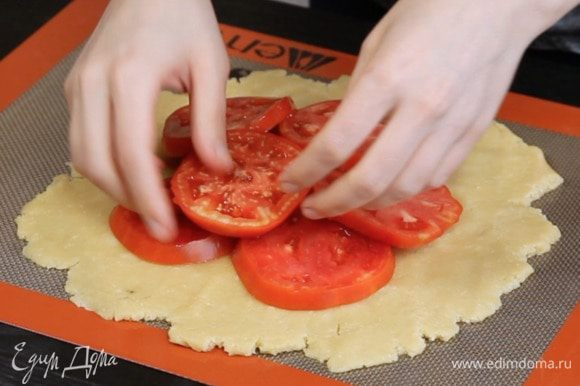Раскатать тесто 4 мм толщиной, выложить в центр помидоры.