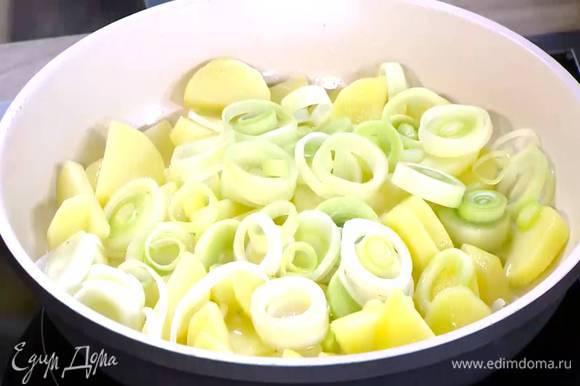 Разогреть в сковороде 2 ст. ложки оливкового масла и обжаривать картофель до появления золотистой корочки, а лук-порей до прозрачности.