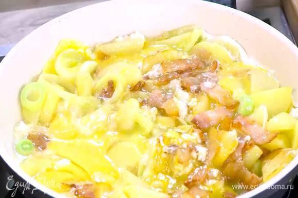 Разбить в сковороду с овощами и беконом яйца, все перемешать.