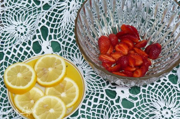 Нарезать клубнику. Сложить в крюшонницу. За ее неимением я воспользовалась двумя салатниками. Лимон нарезать кольцами и добавить к клубнике.