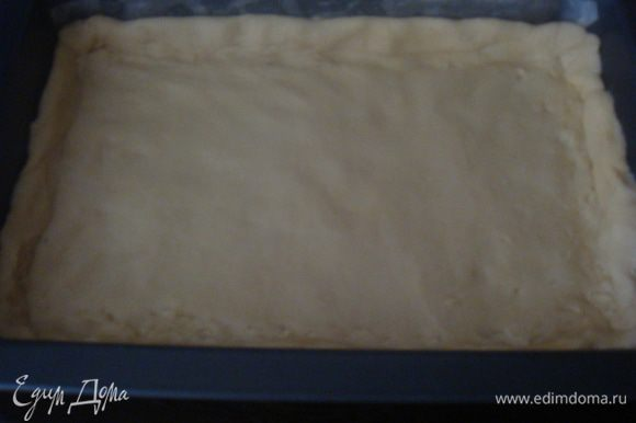 Форму застелить бумагой для выпечки. Тесто раскатать по размеру формы и переложить в форму, сделать не большие бортики, примерно 1 см.