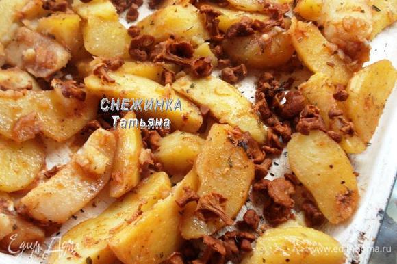 Вынимаем из горячей духовки противень, выкладываем картофельные дольки на противень. Сверху распределяем лисички. Ставим запекаться при 220-230°C на 20 минут.