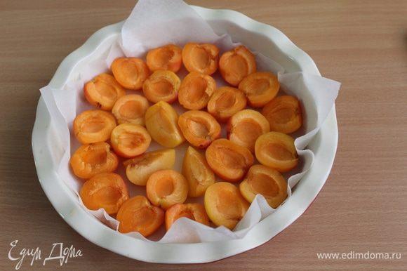 Форму 22 см застелить бумагой для выпечки, выложить дольки абрикос верх срезом.