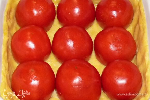 Выложить на тесто фаршированные помидоры срезом вниз.