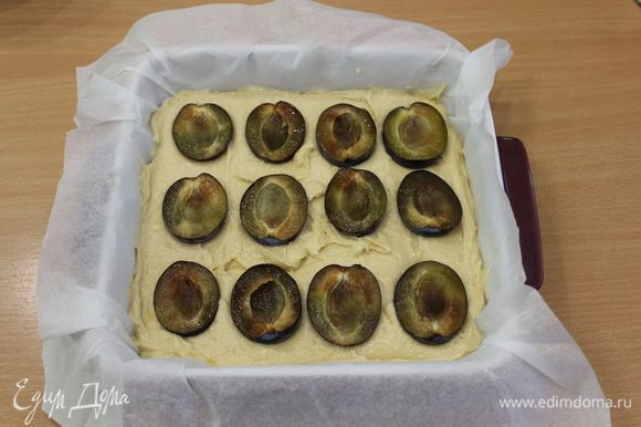 Выложить тесто в форму, сверху половинки слив, слегка вдавив их.