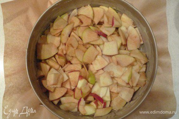 Дно круглой разъемной формы (у меня диаметром 24 см) выстелить пергаментом. Смазать дно и бока формы небольшим количеством сливочного масла и выложить яблоки на дно формы.