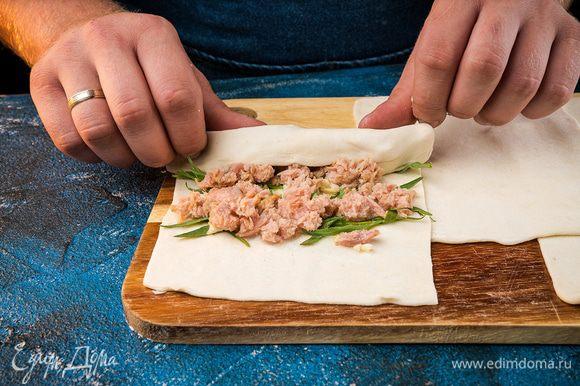 В отдельной миске перемешать начинку: тунца и чеснок. Выложить и равномерно распределить начинку по тесту, добавить к начинке эстрагон.