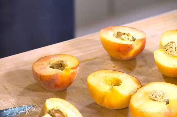 Персики разрезать пополам и удалить косточки.