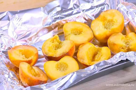Небольшой противень выстелить пищевой фольгой, выложить персики, срезами вверх, посыпать сахарной пудрой и отправить на 2 минуты под разогретый гриль.