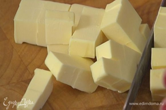 Предварительно охлажденное сливочное масло нарезать небольшими кусочками.