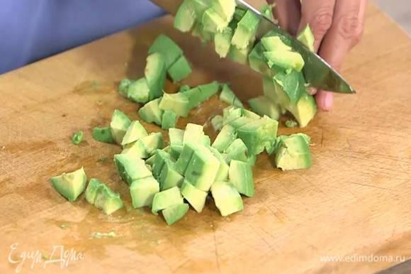 Авокадо разрезать пополам и, удалив кожуру и косточку, нарезать небольшими кубиками.