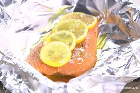Небольшой противень выстелить фольгой, выложить форель кожей вниз, посолить, поперчить, сверху разложить кружки лимона. Слегка сбрызнуть рыбу оливковым маслом и запекать под разогретым грилем 5‒7 минут.