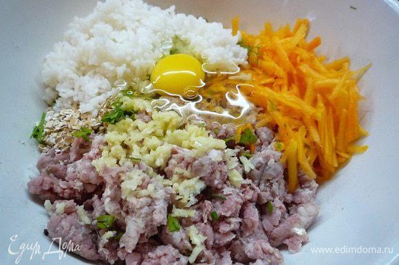 В фарш добавляем мелко рубленную зелень, отваренный до полуготовности рис, яйцо, чеснок, овсяные хлопья, натертую на крупной терке тыкву. Солим, перчим.