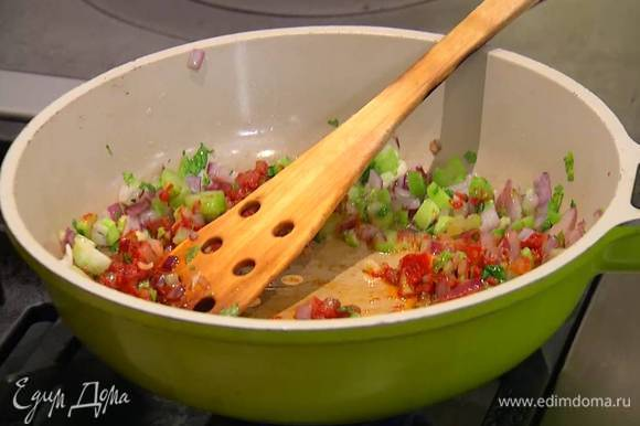 К обжаренному луку добавить сельдерей, чеснок и томатную пасту, все перемешать.