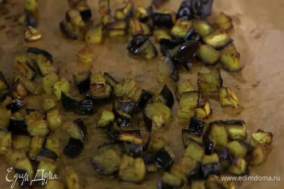 Противень выстелить бумагой для выпечки, выложить нарезанный баклажан, слегка посолить, поперчить, посыпать зирой, немного сбрызнуть оливковым маслом и запекать в разогретой духовке 10‒15 минут.