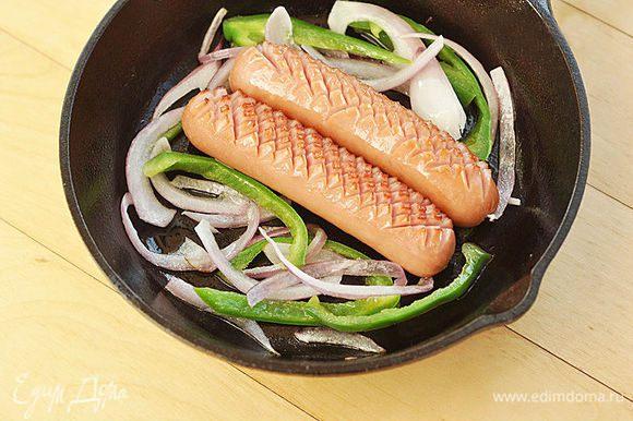 Положить на сковороду сосиски и обжарить их с двух сторон в течение 2—х минут на среднем огне.