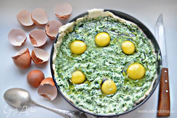 В начинке сделайте 6 выемок и вбейте туда яйца.