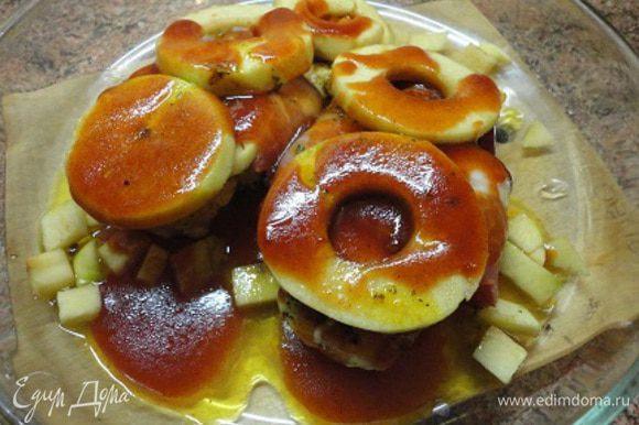 Стейки обжарить с двух сторон, обернуть полосками копченой грудинки. Выложить в форму, сверху яблоки и полить глазурью. Запекать в духовке 15 минут при температуре 200°С.