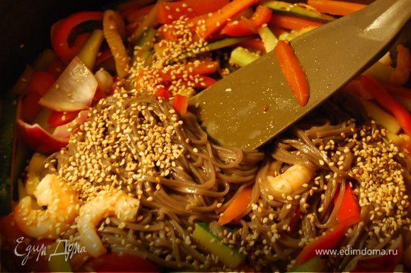 В закипевшую воду бросить 100 гр гречневой лапши и подержать там 5 минут. Через 5 минут откинуть лапшу на дуршлаг, и отряхнув от воды выложить в сковороду к овощам и хорошо перемешать.Добавитьнемного кунжутного масла, посыпать кунжутными семечками. Попробовать на вкус, если вкус недостаточно соленый добавить соевого соуса. Выложить в миску.Одну общую или сразу в порционные. Украсить водорослями. Как вариант можно подать с мелко порезанными нори.