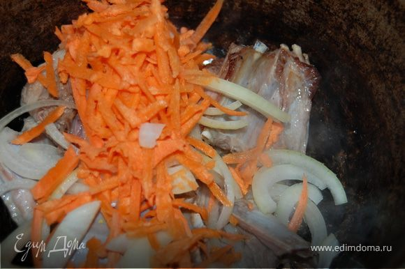 Моем баранину, нарезаем по ребрышку, укладываем в казан. За неимением курдюка, добавила немного растительного масла и начала обжаривать. К зарумянившимся ребрам выкладываю лук полукольцами и натертую на крупной терке морковку, обжариваю, как для плова.