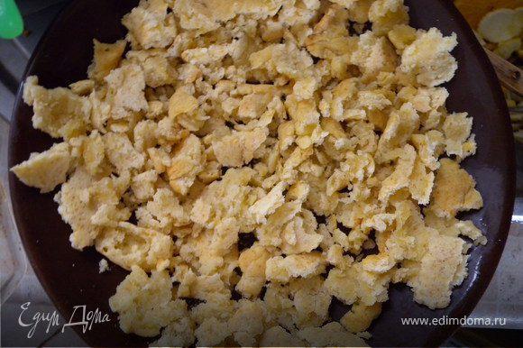 Порвать корж на кусочки, выложить на форму или тарелку для микроволновки, немного примять.