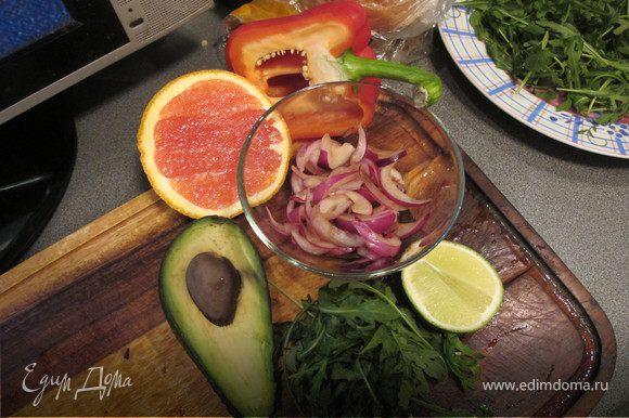 Выложить на тарелку руколу, перец, нарезанный полосочками, чайной ложкой сформировать кружочки из авокадо, выложить на салат. Лук нарезать перышками и замариновать в соевом соусе и уксусе на пару минут. Выложить на салат.Мякоть апельсина отделить от всех перепонок и выложить на салат.