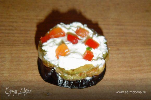На баклажаны укладываем кружки кабачков, смазываем его творожным сыром и засыпаем зеленью и сладким перцем.