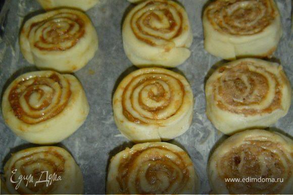 Форму , застелить промасленной бумагой, уложить булочки на небольшом расстоянии друг от друга срезами вверх,дать постоять минут 15, накрыв полотенцем, а затем смазать желтком и посыпать сахаром.