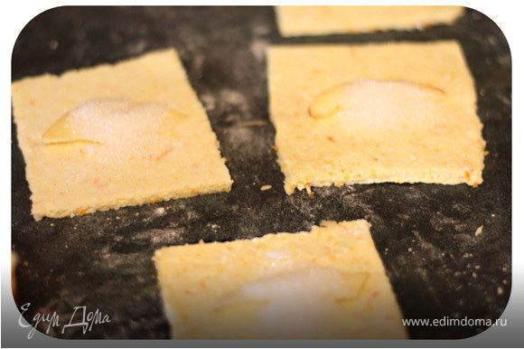 Тесто раскатать в пласт толщиной 3-5 мм. Нарезать квадратики 8х8 см. Каждый квадратик посыпать сахаром и положить небольшой кусочек яблока ( можно еще посыпать корицей)